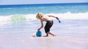 Criança loura que enche sua cubeta com água filme