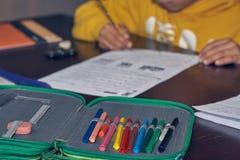 A criança masculina é concentrada muito que faz seus trabalhos de casa na mesa em seu lugar fotos de stock