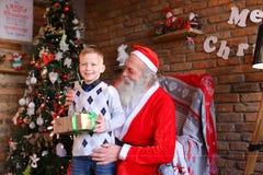 A criança masculina curiosa recebe o presente de Santa Claus em f decorado Foto de Stock