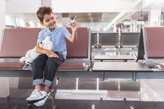 Criança masculina de sorriso interessada que localiza no terminal imagem de stock