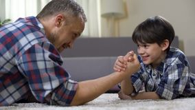 Criança masculina pequena que desafia seu pai na luta romana de braço, tendo o divertimento junto filme