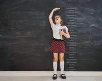 A criança mede o crescimento no fundo do quadro-negro fotografia de stock