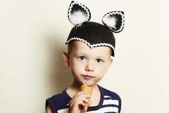 Criança. menino bonito da criança que come o gelado em studio.masquerade Fotos de Stock Royalty Free