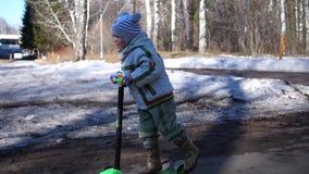 A criança monta um 'trotinette' no parque na mola adiantada Neve de derretimento, neve e poças no asfalto Esportes ao ar livre vídeos de arquivo