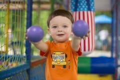 A criança mostra bolas do brinquedo Brincadeiras no centro do ` s das crianças imagem de stock royalty free