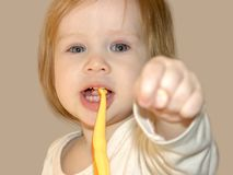A criança mostra o punho com o polegar entre o meio e o indicador imagem de stock