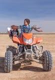 Criança na área do deserto de ATV Imagens de Stock