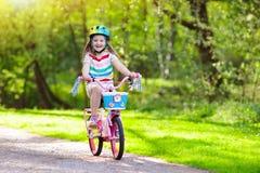 Criança na bicicleta Bicicleta do passeio das crianças Ciclismo da menina fotos de stock