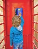 Criança na caixa de telefone Imagens de Stock