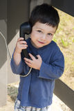 Criança na caixa do telefone Fotos de Stock