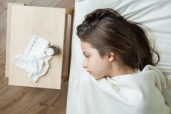 A criança na cama travou em casa frio, tomando medicinas, estação de gripe imagem de stock