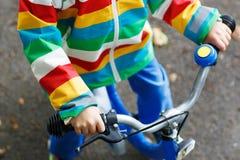Criança na capa de chuva colorida que monta sua primeira bicicleta Fotografia de Stock Royalty Free