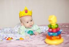 A criança na coroa encontra-se em uma cama com brinquedos Imagens de Stock