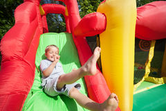 Criança na corrediça bouncy inflável do castelo fotos de stock royalty free