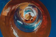 Criança na corrediça colorida Criança que escala e que desliza no pla exterior foto de stock