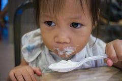 A criança na cozinha com uma colher come o grito do gelo fotografia de stock
