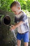 Criança na fonte da tubulação de água potável. fotografia de stock