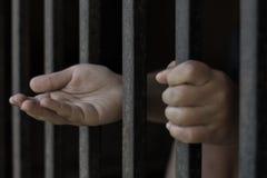 A criança na gaiola de ferro estendeu sua mão, o conceito da ajuda imagens de stock royalty free