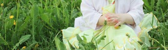 Criança na grama com uma maçã em suas mãos fotos de stock royalty free