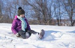 A criança na neve desliza no tempo de inverno Foto de Stock Royalty Free