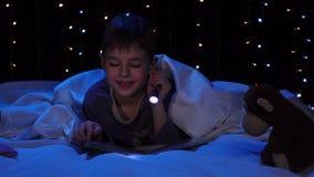 Criança na noite que lê um livro na cama Fundo de Bokeh video estoque