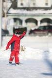 Criança na patinagem de gelo vermelha no parque público Foto de Stock