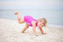 A criança na praia é contratada na ioga foto de stock royalty free