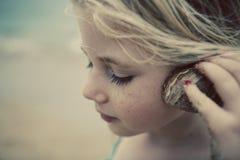 Criança na praia com Seashell Fotos de Stock Royalty Free