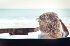 Criança na praia que olha no mar da distância com horizonte durante o estilo de vida do curso da infância das férias das férias d imagem de stock