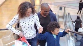 Criança na viagem ao shopping com pais na escada rolante vídeos de arquivo