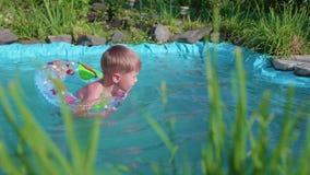 A criança nada em um círculo inflável em uma lagoa pequena Área, flores e plantas do jardim em torno do lago feliz video estoque