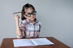 A criança Nerdy pensa sobre o que escrever Foto de Stock