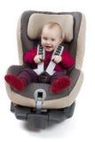 Criança no assento do impulsionador para um carro no fundo claro imagem de stock