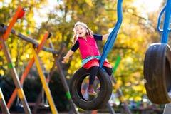 Criança no campo de jogos no outono Crianças na queda fotos de stock