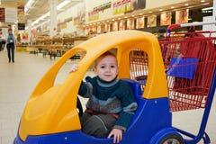 Criança no carro de compra Foto de Stock Royalty Free