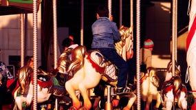 Criança no cavalo no carrossel Fotos de Stock
