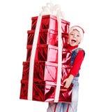 Criança no chapéu de Santa com a caixa de presente da pilha. Foto de Stock Royalty Free