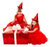 Criança no chapéu de Santa com a caixa de presente vermelha do Natal. Fotos de Stock Royalty Free