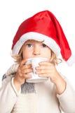 Criança no chapéu de Santa que bebe o chocolate quente Imagens de Stock