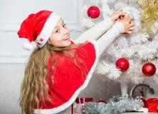 Criança no chapéu de Santa que decora a árvore de Natal Conceito da tradição da família Criança que decora a árvore de Natal com  imagens de stock royalty free