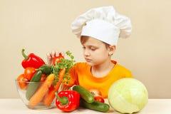 A criança no chapéu dos cozinheiros chefe escolhe vegetais para a salada na tabela Imagem de Stock Royalty Free