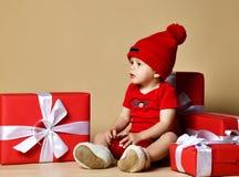 Criança no chapéu vermelho com as pilhas das caixas atuais em torno do assento no assoalho fotos de stock