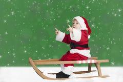 Criança no equipamento de Papai Noel em um pequeno trenó, olhando acima Fotografia de Stock