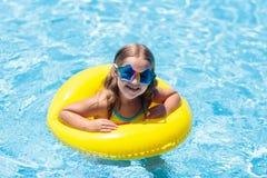 Criança no flutuador na piscina Óculos de sol das crianças fotografia de stock royalty free