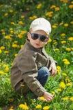 A criança no gramado da grama verde com dente-de-leão floresce no dia de verão ensolarado Criança que joga no jardim Foto de Stock