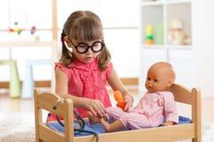 Criança no jardim de infância Criança no infantário Menina que joga o doutor com boneca imagem de stock
