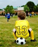 Criança no jogo de futebol de observação uniforme Fotografia de Stock Royalty Free