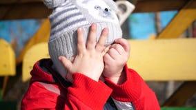 A criança no jogo do divertimento do parque, andando no ar fresco Cobre sua cara em suas mãos, embaraçado Um bonito video estoque