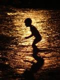 Criança no mar no por do sol Fotos de Stock Royalty Free