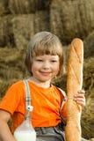 Criança no monte de feno com pão e leite Fotografia de Stock Royalty Free